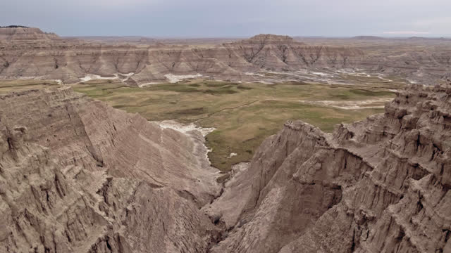 DRONE. Aerial view between high Badlands rock formations towards serene green valley