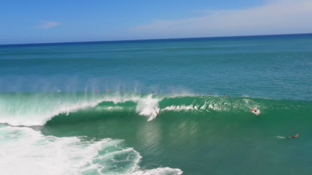 stockvideo's en b-roll-footage met aerial view blue ocean & bodysurfers catching a wave at pipeline, hawaii - oahu