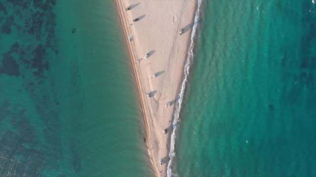 aerial view by a drone of potamos or epanomi beach with miti or the sandbank on the edge of the beach near thessaloniki city in greece on july 6 2019... - thessalonika stock videos & royalty-free footage