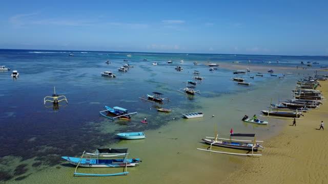 4K: vista aérea de secuencias del abejón Mertasari playa en Sanur.Some barcos de pesca tradicionales (jukung) estacionados en aguas poco profundas.
