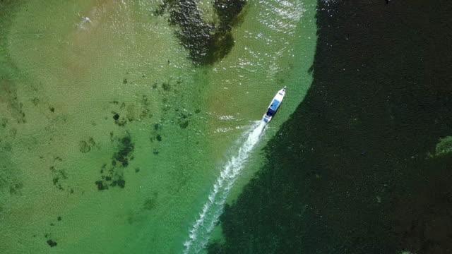 vidéos et rushes de 4k: vue aérienne de footage de drone mertasari beach en sanur.some des bateaux de pêche traditionnels (jukung) sont stationnés dans les eaux peu profondes. - bali