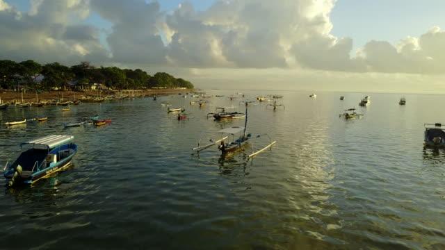 vídeos y material grabado en eventos de stock de 4k: vista aérea de secuencias del abejón mertasari playa en sanur.some barcos de pesca tradicionales (jukung) estacionados en aguas poco profundas. - cultura indonesia