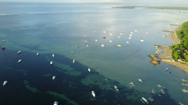 4K : Aerial view by drone footage Mertasari beach in Sanur.Some traditional fishing boats (jukung) are parked in the shallow water.