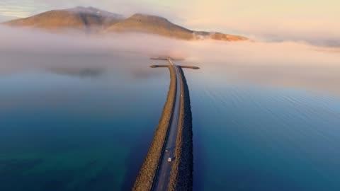 vídeos de stock e filmes b-roll de ws aerial view car moving along road over remote mountain lake,iceland - islândia