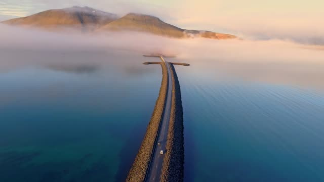 ws aerial view car moving along road over remote mountain lake,iceland - automobile video stock e b–roll