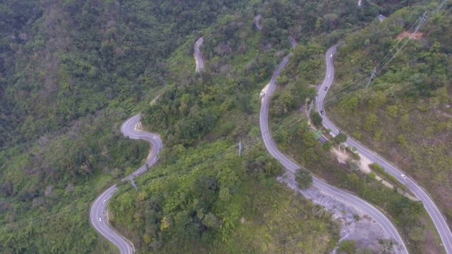 Aerial view cars driving along the  winding mountain pass road through the forest
