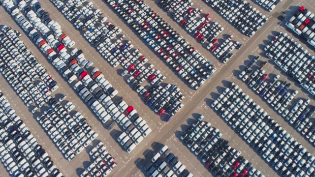 ws aerial view cars parked in sunny parking lot - automobile industry video stock e b–roll