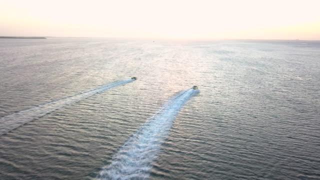 aerial view chasing fast motor boats in the caribbean - motoscafo da competizione video stock e b–roll