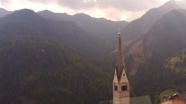 ws aerial view church steeple overlooking majestic mountains, dolomites, italy - monumento video stock e b–roll