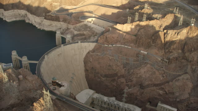 aerial view circling the hoover dam during sunset - hydroelectric power stock videos and b-roll footage