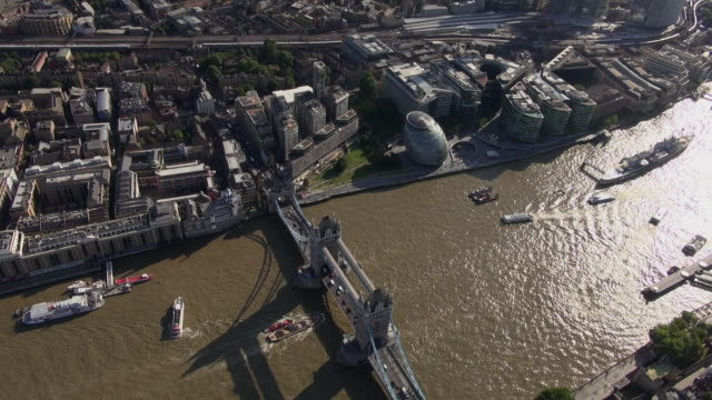 Aerial view circling Tower Bridge and immediate vicinity, including London Bridge area and City Hall on south bank and Tower of London on north bank