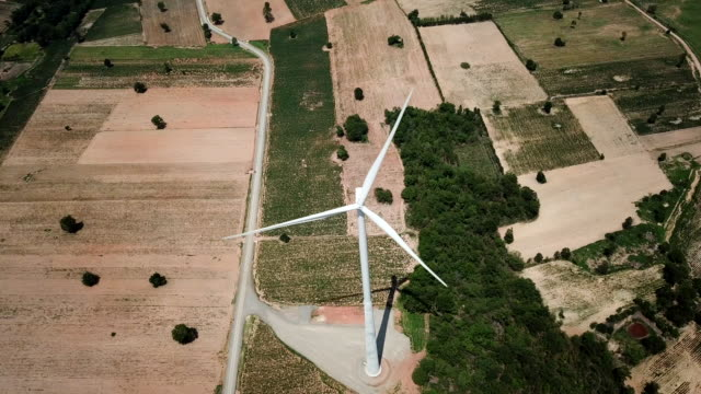 aerial view clean electric wind farm turbine generating electricity energy production with clean and renewable energy - power in nature stock videos and b-roll footage