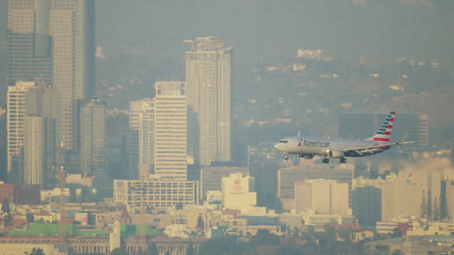 aerial view commercial skyscrapers aircraft landing los angeles - aerospace stock videos & royalty-free footage