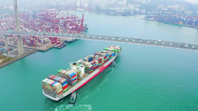 vídeos de stock e filmes b-roll de aerial view container cargo ship going to terminal commercial port or container warehouse with hong kong cityscape for business logistics, import export, shipping or transportation. - navio cargueiro