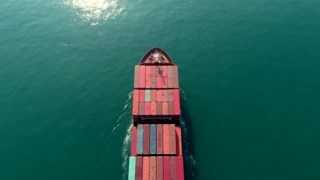vidéos et rushes de aerial view container ship full load container on the green sea for logistics , shipping , import export or transportation. - faire fonctionner