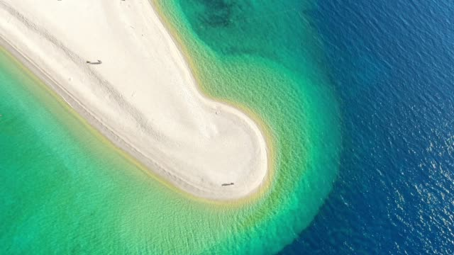 aerial view couple flying drone off sunny,tranquil beach on bol - zlatni rat,island of brac,croatia - zoom out stock videos & royalty-free footage
