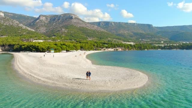 ボル - zlatni ラット、ブラチ島の島、クロアチアに日当たりの良い、静かなビーチを離れて空中ビュー カップル飛行ドローン - ブラック島点の映像素材/bロール