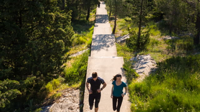 ws aerial view, couple running uphill through forest - steil stock-videos und b-roll-filmmaterial
