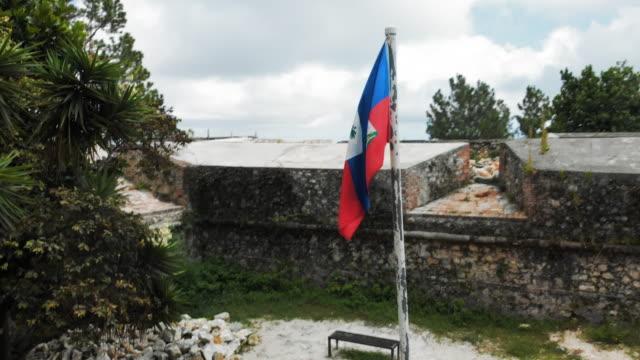 vídeos y material grabado en eventos de stock de aerial view couple sitting on bench outside citadel in haiti - hispaniola