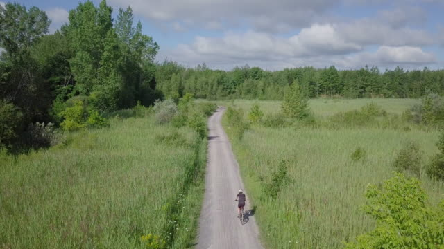 stockvideo's en b-roll-footage met 4k luchtfoto fietsen in de natuur - footpath