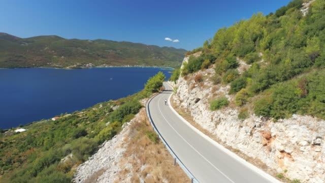ws aerial view cyclist bike riding on sunny island road,viganj,croatia - coastal road stock videos & royalty-free footage