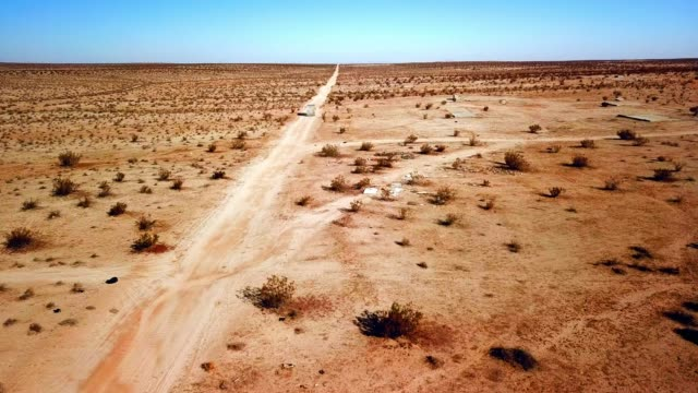 aerial view: desert landscape with dirt roads, truck & building foundations - josuabaum stock-videos und b-roll-filmmaterial