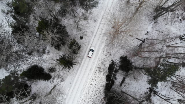 aerial view directly above of car driving in the snowy landscape of sweden. - parabrezza video stock e b–roll