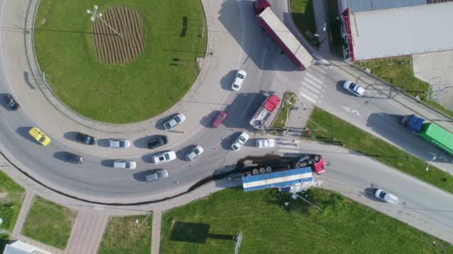 aerial view directly above over a traffic jam caused by a truck crash in the middle of a busy roundabout, top view, cityscape. accidents and disasters. - transportation event stock videos & royalty-free footage