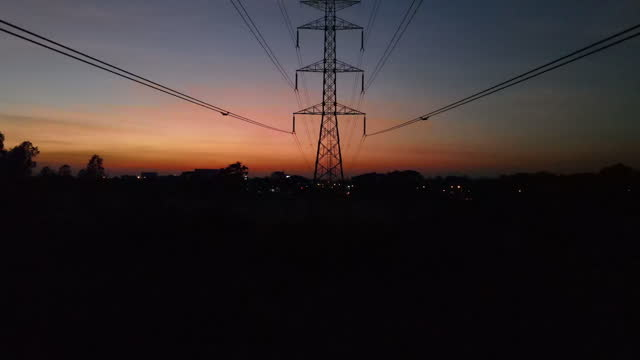 aerial view dolly below high voltage power line electricity pylons at sunset twilight - power line stock videos & royalty-free footage