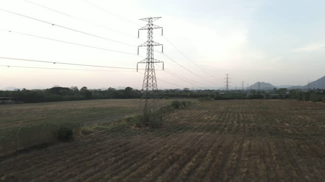 aerial view dolly of high voltage power line electricity pylons in the field in the evening before sunset - high voltage sign stock videos & royalty-free footage