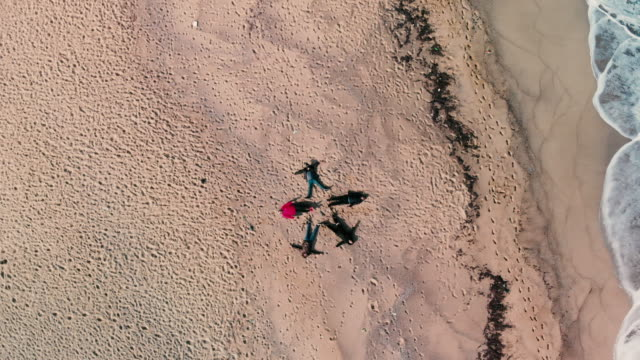 aerial view drone point of view of young man lying like star shape on beach - byakkaya stock videos and b-roll footage