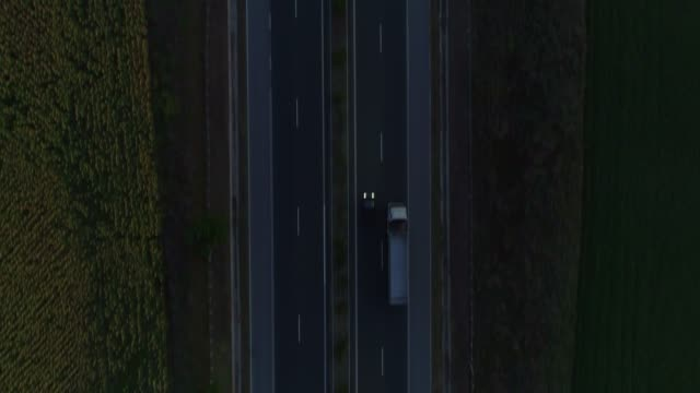 aerial view drone revealing flying over highway after sunset - heavy goods vehicle stock videos & royalty-free footage