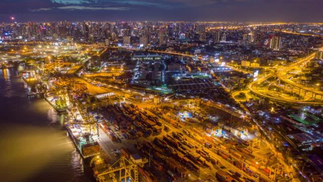 多くのコンテナ船と夜の都市の背景の間で働く大きなクレーンでバンコクタイの工業港上の空中写真ドローンタイムラプスまたはハイパーラプス - ポートワイン点の映像素材/bロール