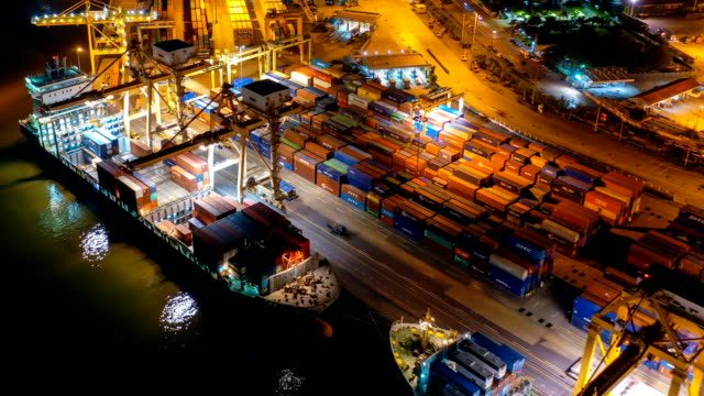 aerial view drone-lapse or time-lapse of industrial port or dockyard with containers ship at night in south east asia - jetty stock videos & royalty-free footage