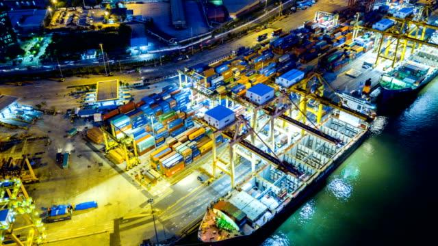 航空写真ビュー ドローン経過または夜のコンテナー船東南アジアでの工業港のコマ撮り - 流通センター点の映像素材/bロール