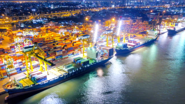 aerial view drone-lapse or time-lapse of industrial port with containers ship at night in south east asia - unloading stock videos & royalty-free footage