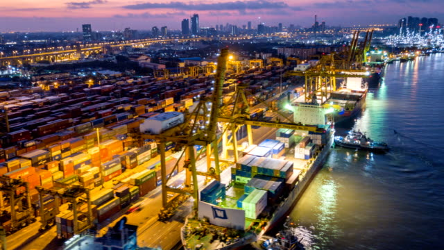 vídeos de stock e filmes b-roll de aerial view drone-lapse or time-lapse of industrial port with containers ship at night in south east asia - transporte de mercadoria