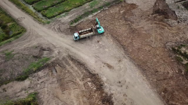 aerial view dumper truck working on place  around paddy field - dumper truck stock videos & royalty-free footage