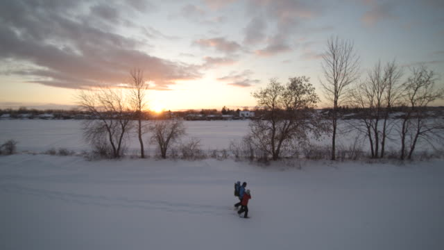 Aerial View Family Snowshoeing Outdoor in Winter at Sunset
