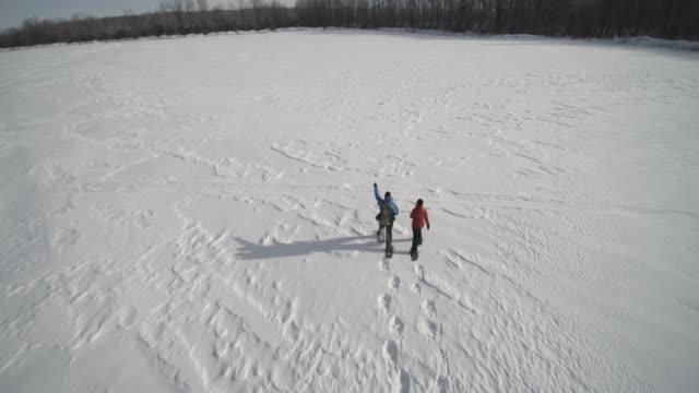 vídeos y material grabado en eventos de stock de vista aérea de familia con raquetas de nieve al aire libre en invierno - pisada
