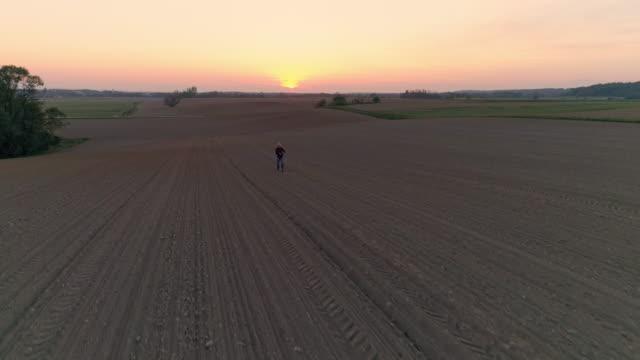 WS-Antenne Ansicht Bauer verbreiten, säen im idyllischen, ländlichen Gepflügtes Feld bei Sonnenuntergang.
