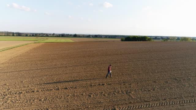 WS-Antenne Ansicht Bauer Wandern in sonnigen, großen, ländlichen Gepflügtes Feld