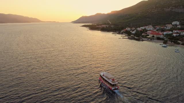 ws の航空写真ビュー フェリー peljesac、クロアチア、夕暮れ時の静かな海に沿って移動 - フェリー船点の映像素材/bロール