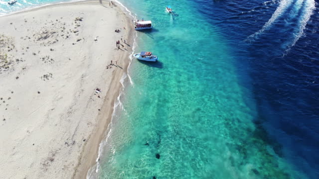 aerial view flying above the turtle island with idyllic beach in greece. - greece stock videos & royalty-free footage