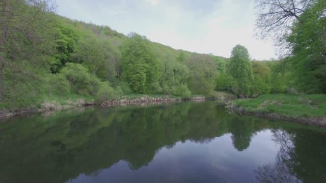 vidéos et rushes de vue aérienne-vol le long d'une rivière dans le parc naturel/4k - valley