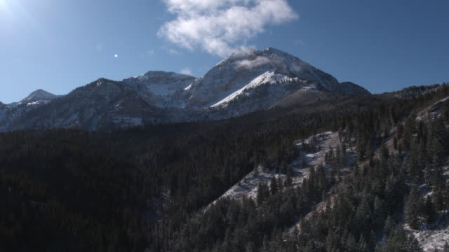 Aerial view flying away from snow covered mountain top