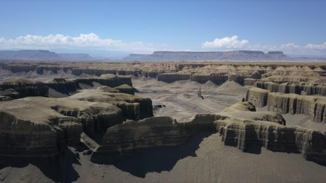 vídeos de stock, filmes e b-roll de aerial view flying backwards from desert cliffs viewing mesa tops - mesa formação rochosa