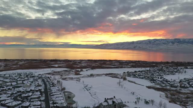 vidéos et rushes de aerial view flying backwards over snow covered urban city landscape at sunset - aménagement de l'espace