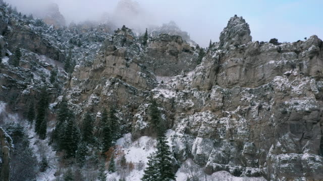aerial view flying between pine trees towards snow covered rocky cliffs - american fork city stock videos & royalty-free footage
