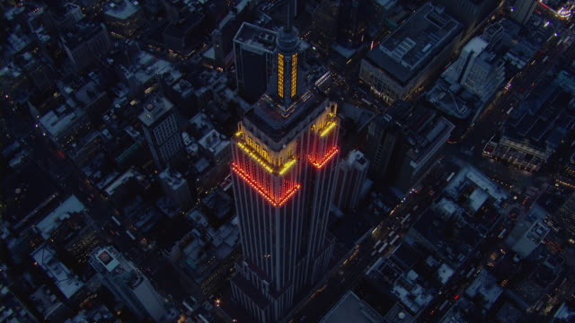 aerial view flying directly over the empire state building at night. - 20世紀のスタイル点の映像素材/bロール